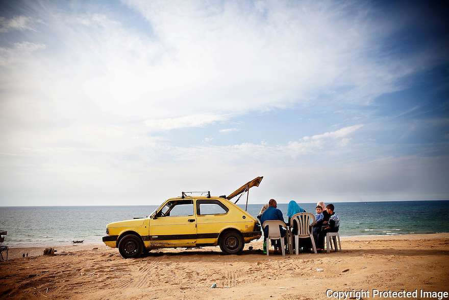 A Gazan family parks the car for an impromptu picnic on Meditteranean. With limited mobility, families of all economic classes make the most out of the sea--some from their cars,  a few from chalets, and public restaurants.