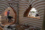 Palestinian workers construct huts using sacks of sand at entertainment area in the north of Gaza Strip, June 7, 2010. Israel's embargo on construction materials supply into Gaza has forced Palestinians to seek alternative sources. Photo by Ashraf Amra