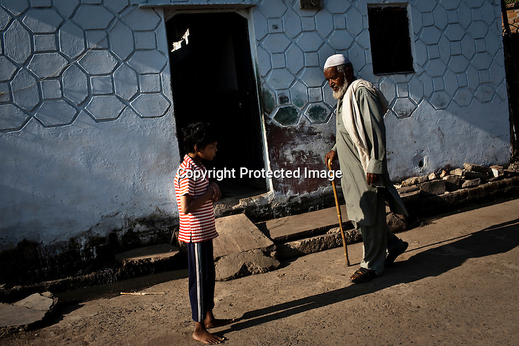 An old man walks past 10 year old Nawab Mian, (who is suffering from mental illness related to the 1984 Bhopal gas disaster) as he stands outside his house in New Arif Nagar  near the site of the deserted Union Carbide factory in Bhopal, India. Nawab Mian couldn't walk for 8 years but after regular phsiotheraphym, he has started walking since last 2 years. Twenty-five years after an explosion causing a mass gas leak, in the Union Carbide factory in Bhopal, killed at least eight thousand people, toxic material from the 'biggest industrial disaster in history' continues to affect Bhopalis. A new generation is growing up sick, disabled and struggling for justice. The effects of the disaster on the health of generations to come, both through genetics, transferred from gas victims to their children and through the ongoing severe contamination, caused by the Union Carbide factory, has only started to develop visible forms recently.  Photograph: Sanjit Das