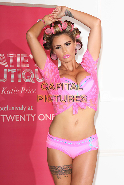 Katie Price (Jordan).The launch photocall for Katie Price's new summer lingerie range for Store 21, The Worx, London, England..May 29th, 2012.half length belly stomach midriff arms in air pink lace top bra cleavage rollers curlers in hair knotted lipstick knickers underwear garter tattoo .CAP/ROS.©Steve Ross/Capital Pictures.