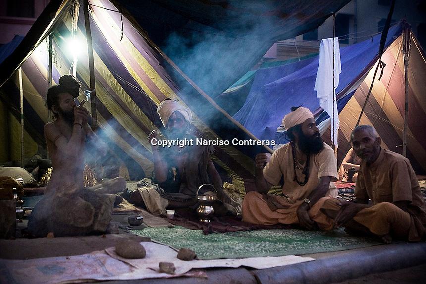 KUMBH MELA. THE NAGA BABAS PROCESSION. A GROU OF SADHUS SADHUS SMOKE HACHIS DURING THE FESTIVAL IN HARIDWAR, INDIA.