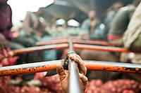 A porters hand on the roll bars of a truck delivering onions to Wakulima market in Naiorbi.