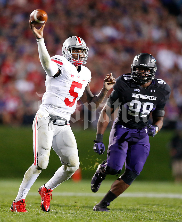 Ohio State Buckeyes quarterback Braxton Miller (5) throws a pass while pursued by Northwestern Wildcats defensive lineman Chance Carter (99) during Saturday's NCAA Division I football game at Ryan Field in Evanston on October 5 2013. (Barbara J. Perenic/The Columbus Dispatch)