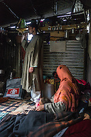 Shugufta, 29 and her husband, goes about their daily lives in their temporary shelter in Narbal village, Jammu and Kashmir, India, on 24th March 2015. When the floods hit in the middle of the night, Shugufta and her family had to walk 5 miles to find shelter. Save the Children supported the family with shelter kits, blankets, hygiene items, food and tarpaulin, which they have used to build a temporary shelter next to their crumbled home. Photo by Suzanne Lee for Save the Children