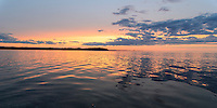 Summer sunset reflections on a glassy Lake Superior. Presque Isle park, Marquette, MI