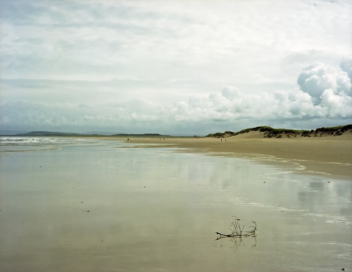 A wet sandy beach in Scotland reflects clouds.