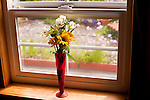 Flower arrangement in vase on window sill with garden outdoors