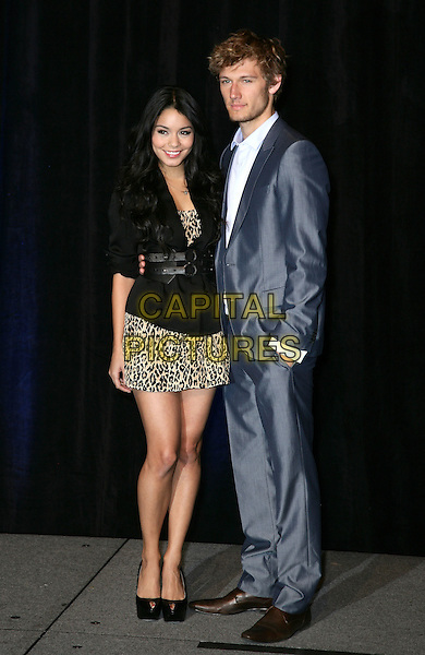 VANESSA HUDGENS & ALEX PETTYFER .CBS Films ShoWest Luncheon at the Paris Resort Hotel and Casino,  Las Vegas, Nevada, USA,.18th March 2010..full length black leopard print dress platform peep toe shoes jacket animal grey gray suit hand in pocket .CAP/ADM/MJT.© MJT/AdMedia/Capital Pictures.