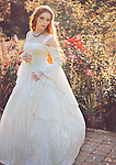A beautiful youthful woman with long red hair, in a pretty garden wearing a traditional wedding gown