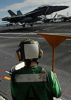 Hook runner waits to guide cables back into place as aircraft recover aboard USS Abraham Lincoln.