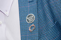"""A campaign staffer wears a Bernie-shaped lapel pin and one reading """"Black Boy Joy"""" at the Iowa State Fair in Des, Moines, Iowa, on Sun., Aug. 11, 2019."""