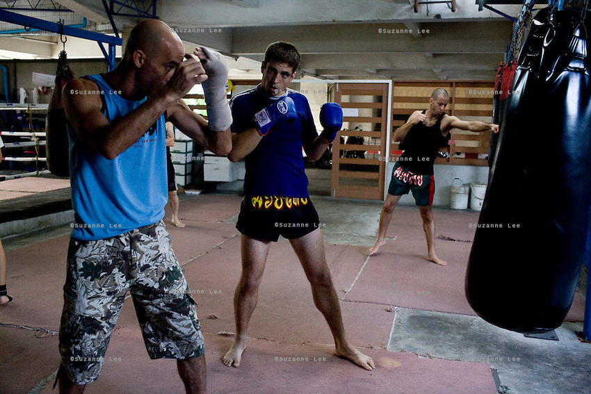 """Shuki (left) coaches Ilya (center) as Eran (right) trains with punching bags in Rompo Muay Thai Gym, Khlong Toei, Bangkok city, Thailand on 14th December 2009..Shuki Rosenzweig, aged 40, is a professional Muay Thai Boxing fighter (champion) and trainer who has lived for 9 years in Thailand. He is famous in Israel as the authority of this sport. Started at the age of 12 in boxing in Israel, Jerusalem. Used to work in the fish market. His father is a 'legend' in Jerusalem fish market. Shuki stopped working with his dad about 13 years ago. He has opened some muay thai gyms in Thailand in the past. He currently has about 5 Israeli fighters under his training in Bangkok, besides fighters of other nationalities. Shuki found religion in Bangkok with Chabad about 4 years ago. He never misses Shabbat and loves to sing the songs of prayer, priding himself with a good voice. """"Chabad integrates all Jews. it keeps us together. When at Chabad, we are at home, united with people of the same culture, language and beliefs""""..Eran Schwartz, aged 30, from Jerusalem, has been training for 8 years. He trains for endurance, fitness and fun, although he has fought in one competition in Bangkok the last time he was here. """"Eran is very talented, technically adept, wise and has a 'good eye' for fights"""" says Shuki. This time Eran is staying 3 and a half months in Thailand to train, travel, and write scripts for a TV show and a cartoon series. He had studied economics and used to work in a bank in Israel before he came here. Eran's grandparents are religious but he grew up being secular. """"Chabad never pushes you to be religious. It is a relaxed place, they accept you for what you are"""" says Eran. """"It is important to go for Shabbat for all Jews on travel."""".Ilya Bashes, aged 27, from Herzeliya, Israel, has been fighting seriously for 5 years. He met Shuki in a muay thai seminar in Israel and decided immediately that he would come to Thailand to train under Shuki. """"I knew he was serious from the lo"""