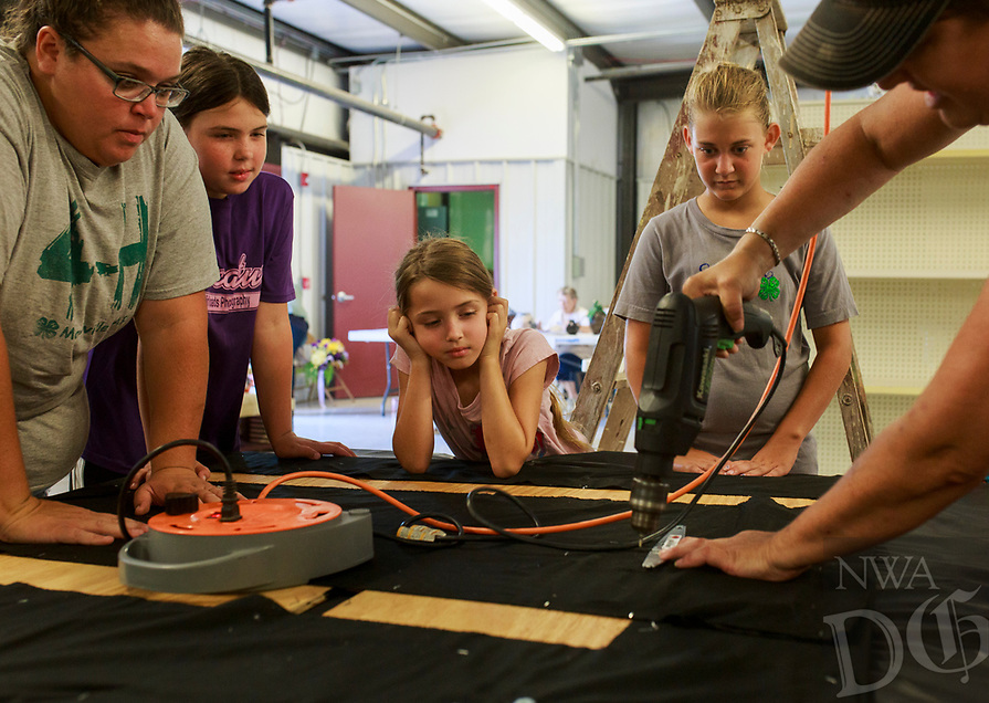 NWA Democrat-Gazette/CHARLIE KAIJO  Shannon Brown of Maysville (right) drills as Tonya Farrister, Kelli McGarrah, 10, Kinzie McGarrah, 7 and Laney Brown, 13, from the Maysville 4-H Club (from left) watch, Saturday, August 4, 2018 at the Benton County Fairgrounds in Bentonville. <br /><br />Vendors prepared their booths ahead of the Benton County Fair which is set to begin August 7.
