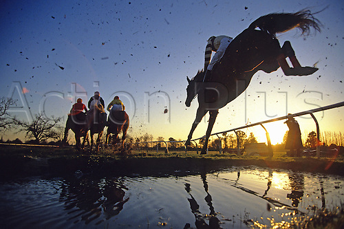 February 1991: Horses and riders are silhouetted against the setting sun as they clear the water-jump during a National Hunt race at Fontwell Park Photo: Mike Hewitt/actionplus...horseracing 9102 silhouette horse sunset water. stock one 50Mb