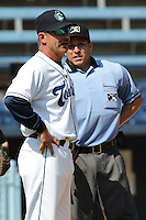 Asheville Tourists manager Joe Mikulik #20 discusses a play with home plate umpire Ivan Mercado during  a  game  against the Hickory Crawdads at McCormick Field on August 7, 2011 in Asheville, North Carolina. Hickory won the game 16-6.   (Tony Farlow/Four Seam Images)
