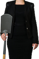 Female executive showing a spade as a metaphor for digging, hard work and earth moving