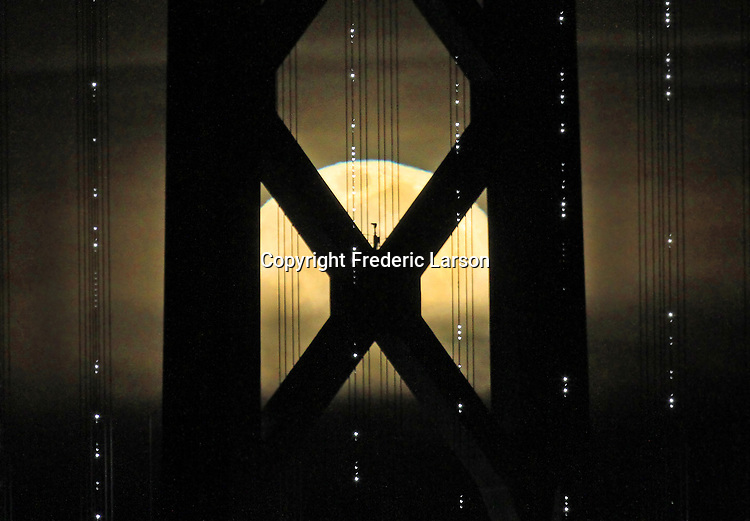 Full Super moon rising behind the Oakland Bay Bridge seen from Pier 1, San Francisco, CA.