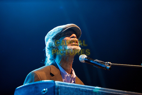 GIL SCOTT HERON.Performing live in concert at Somerset House, London, England, UK, .14th July 2010..music concert gig on stage portrait headshot cap hat microphone beard facial hair piano keyboard .CAP/MAR.© Martin Harris/Capital Pictures.