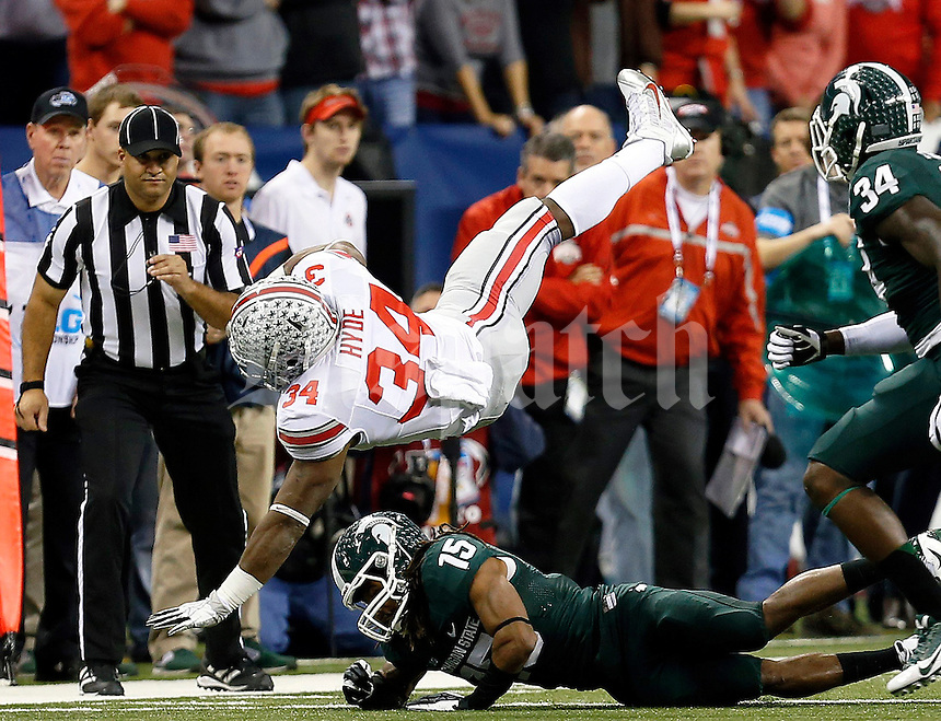Ohio State Buckeyes running back Carlos Hyde (34) gets upended by Michigan State Spartans cornerback Trae Waynes (15) during the first half of the Big Ten Championship football game at Lucas Oil Stadium in Indianapolis on Friday, December 7, 2013. (Columbus Dispatch photo by Jonathan Quilter)