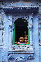 """A woman and child looking out over the blue city of Jodhpur. Jodhpur is affectionately called the """"Blue City"""" because of the blue  houses under and around Mehrangarh Fort. Locals believe the buildings were painted blue to make things appear cooler because of the extreme heat of the area, as well as to add a dash of color to the sandy terrain."""