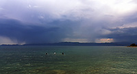 WEATHER PICTURE<br />Three swimmers in the sea as dark clouds and rain seen over the bay of south Evia minutes before a monsoon type storm hits Nireas beach near Aliveri on the island of Evia, Greece. The country has been experiencing recent heatwaves. Thursday 27 July 2017