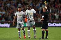 Paul Pogba of Manchester United is shown a yellow card by referee Jonathan Moss during West Ham United vs Manchester United, Premier League Football at The London Stadium on 10th May 2018