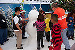Children playing in the snow and building a snowman at Grinchmas at Universal Studios Hollywood in Los Angeles, CA