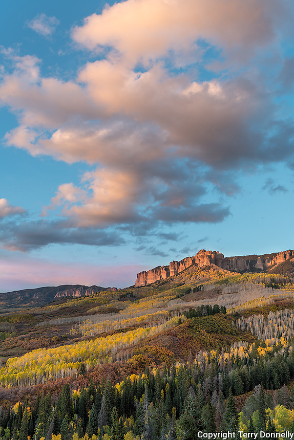 Uncompahgre National Forest, Colorado:<br /> Cliffs of the Cimarron stand above fall colored hillsides, San Juan Mountains