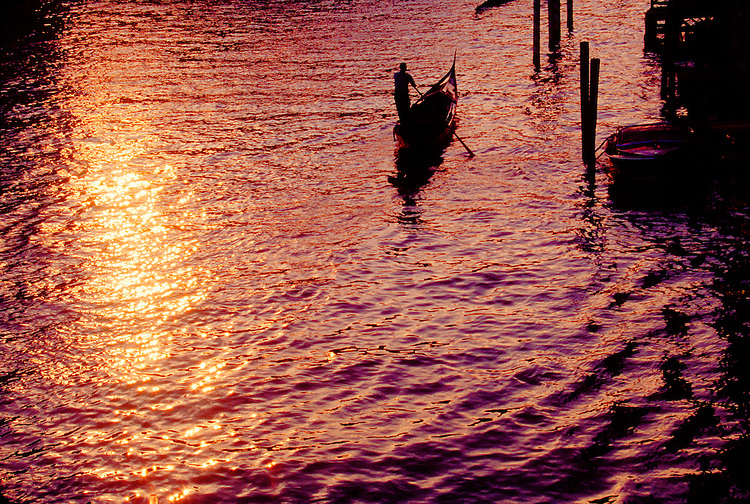 Venice, Italy, Gondola, Grand Canal, gondolier in motion from above and behind in sunset afterglow.