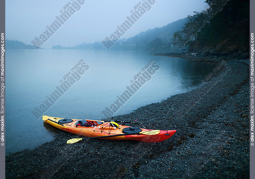 Red kayak with a fishing rod on the shore of Salish sea in yearly misty morning. Nanaimo, Vancouver Island, British Columbia, Canada. Image © MaximImages, License at https://www.maximimages.com