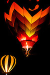 Photo by Phil Grout..Two balloons glow in the darkness as pilots ignite the liquid propane fuel providing intense heat to lift each craft.
