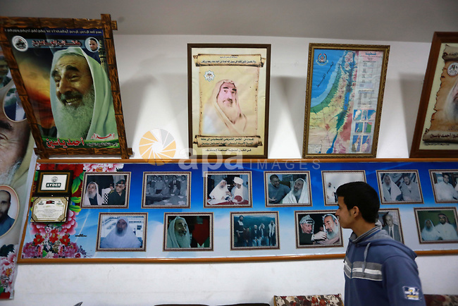 A Palestinian youth walks past pictures for late Hamas leader Sheikh Ahmed Yassin who was killed in an Israeli attack, in his house marking the thirteenth anniversary of his death, in Gaza City, March 21, 2017. Photo by Mohammed Asad