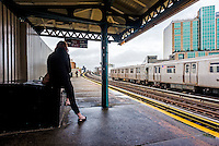 Astoria, New York - 7 April 2016 - Subway commuter waiting on the plaform of an elevated subway platform in Queens.