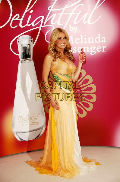 "MELINDA MESSENGER.Launch her new fragrence ""Delightful"" at Vanilla, London, England..December 2nd, 2008 .perfume full length yellow orange green sheer dress cleavage bottle white .CAP/TTL.© TTL/Capital Pictures."