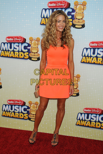 Denise Richards.At the Radio Disney Music Awards 2013 held at Nokia Theatre LA Live, Los Angeles, California, USA, .27th April 2013..full length orange dress smiling tanned sun tan sandals t-bat shoes gold clutch bag bracelet .CAP/ADM/BP.©Byron Purvis/AdMedia/Capital Pictures