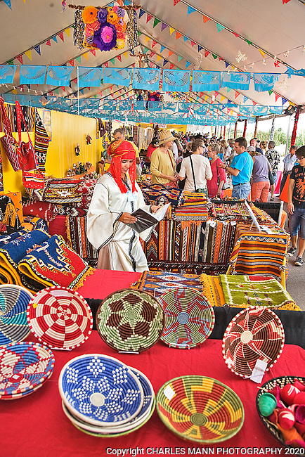The Santa Fe International Folk Art Market attracts a huge crowd of shoppers and features a wide variety of folk artists from all over the world. Moroccan weaver Rkia Ait El Hsasn issurrounded by colorful baskets adn  other works at the June 2011 event.