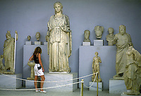 Tourist examines a variety of marble sculptures taken from archaeological sites around Greece. National Museum of Archeology.