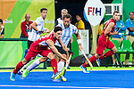 Tanguy Cosyns #32 of Belgium passes the ball while Juan Gilardi #4 of Argentina covers during Argentina vs Belgium  in the men's gold medal game at the Rio 2016 Olympics at the Olympic Hockey Centre in Rio de Janeiro, Brazil.