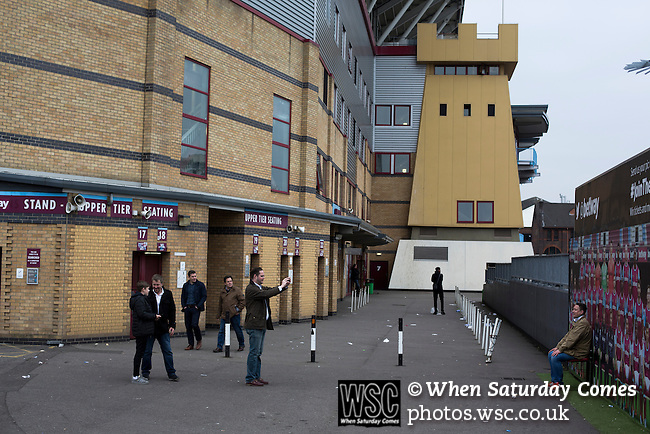 West Ham United 2 Crystal Palace 2, 02/04/2016. Boleyn Ground, Premier League. A fan poses for a photograph outside the Betway Stand at the Boleyn Ground, pictured after West Ham United hosted Crystal Palace in a Barclays Premier League match. The Boleyn Ground at Upton Park was the club's home ground from 1904 until the end of the 2015-16 season when they moved into the Olympic Stadium, built for the 2012 London games, at nearby Stratford. The match ended in a 2-2 draw, watched by a near-capacity crowd of 34,857. Photo by Colin McPherson.