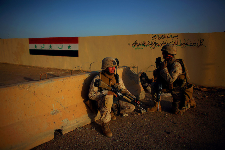 A Marine passes from 2nd BN 5th Marines takes a knee before a newly painted Iraqi flag on a wall during a patrol through central Ramadi on Tuesday May 10, 2007. In recent weeks and months, Ramadi, the provincial capital of the turbulent al-Anbar province has turned from one of the most deadly places in Iraq into an island of relative stability as tribal leaders there have split from the insurgency after years of killings and intimidation.