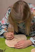Kinder basteln Blattkacheln aus Salzteig, Mädchen malt den Abdruck von einem Eichenblatt auf dem Salzteig an