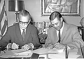 Washington, DC - July 6, 2009 -- Former United States Secretary of Defense Robert S. McNamara, Architect of Vietnam War, died in his sleep at his home in Washington in the early morning of Monday, July 6, 2009. McNamara, who served as Secretary of Defense under Presidents Kennedy and Johnson, was 93.  This file photo from November 14, 1964 shows Minister of Defense Kai-Uwe von Hassel of West Germany, left, and Secretary McNamara, right, signing a research ad development agreement after 2 days of meetings at the Pentagon..Credit: Arnie Sachs / CNP