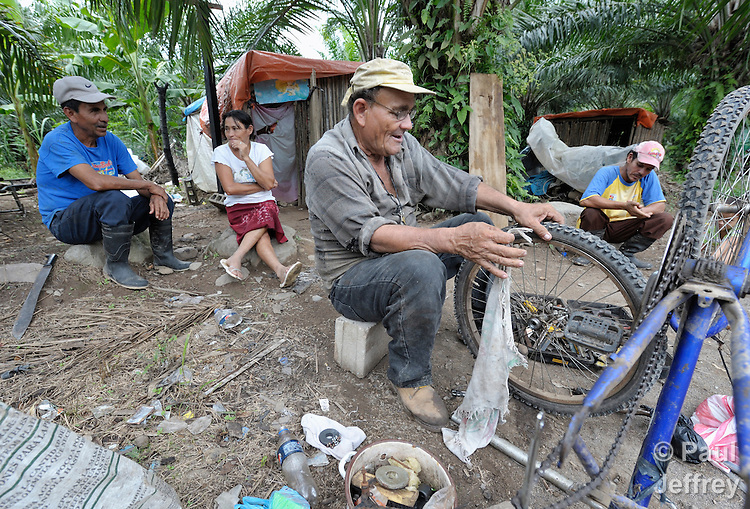 A man repairs a bicycle on the La Lempira Cooperative, near Ceibita, Honduras. La Lempira is an agricultural project which has been seized by armed peasants who claim the land is rightfully theirs under the country's agrarian reform law.