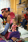 Dr Jamie is playing harmonica for the pleasure of Jake and his sister. The mother in the back is relieved to see his children smiling and relaxed. Sheffield Children's Hospital.