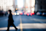 Blurred silhoueted person walking across busy intersection on city street.