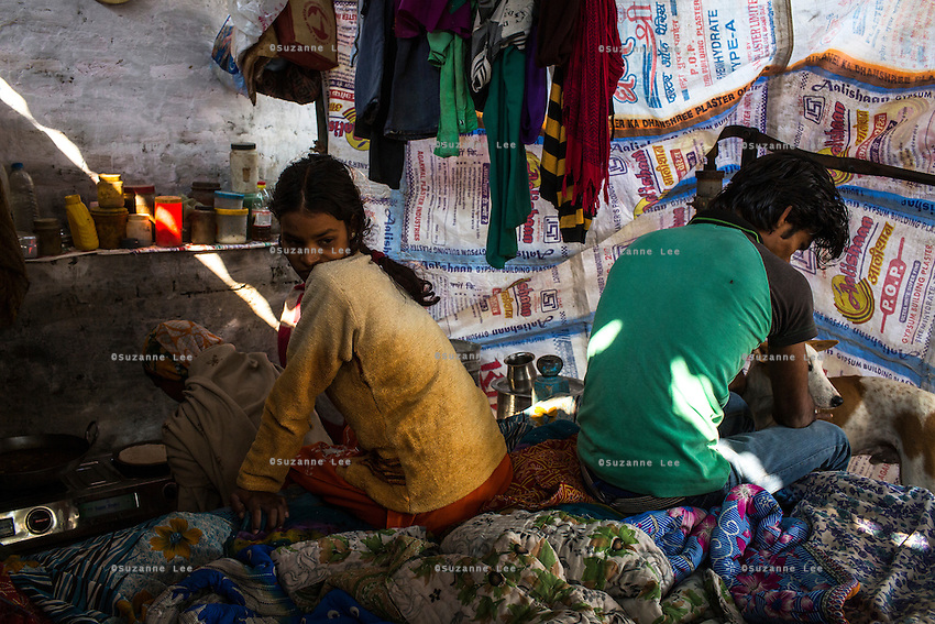 Meera (center) and her brother looks on as their mother makes breakfast in their shelter where they live and work as earring makers in Varanasi, Uttar Pradesh, India on 19 November 2013.