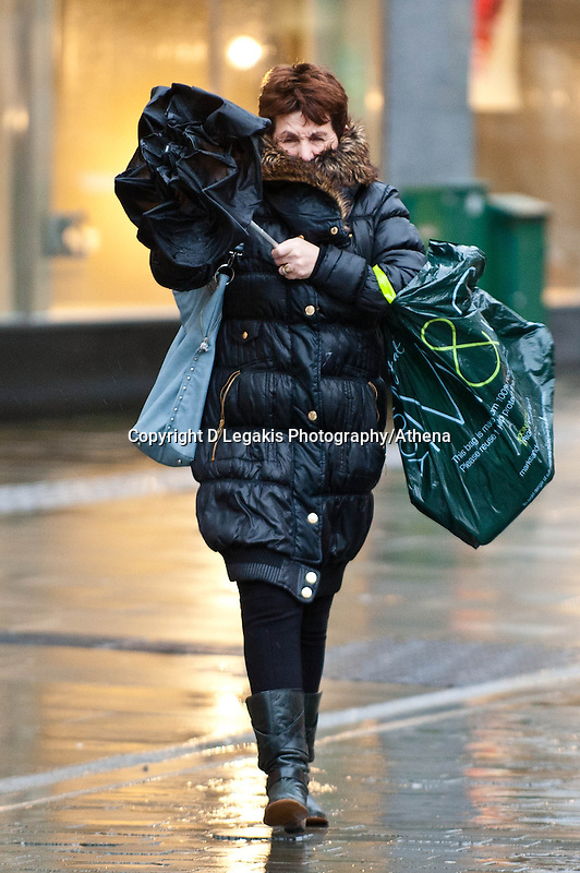 Wednesday 12 February 2014<br /> Pictured: A woman Struggles to get her umbrella up in the strong wind <br /> Re: People struggle with the high winds in the center of Swansea. The met office has today issued more warnings of extreme weather over the next few days.
