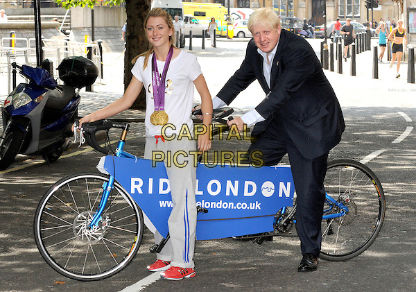 Boris Johnson and Laura Trott.Mayor Of London's Cycling Press Conference, London Media Centre, London, England..August 10th 2012.full length white t-shirt medals tandem bicycle black suit blue shirt .CAP/BK.PP.©Bob Kent/PP/Capital Pictures.