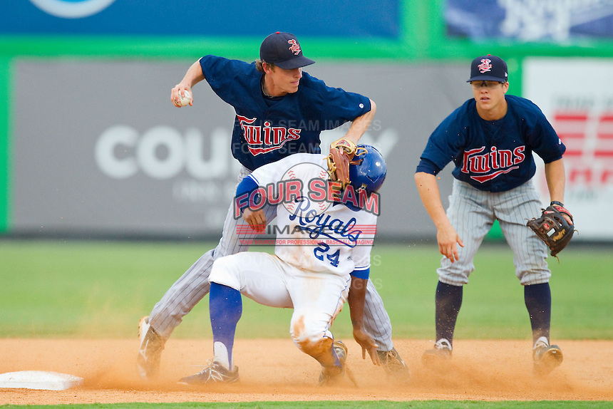 Alex Newman (24) of the Burlington Royals breaks up a double play as he slides into Elizabethton Twins shortstop Ryan Walker (18) at Burlington Athletic Park on August 11, 2013 in Burlington, North Carolina.  The Twins defeated the Royals 12-5.  (Brian Westerholt/Four Seam Images)