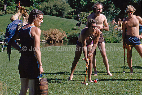 Hugh Hefner, left with parrot on shoulder, watches croquet game on grounds of Playboy Mansion, Los Angeles, 1973. Photo by John G. Zimmerman.